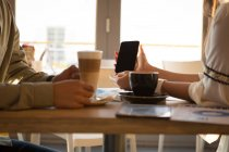 Mid section of couple discussing on mobile phone in cafe — Stock Photo