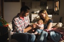 Родители, весело с ребенком на диване у себя дома — стоковое фото