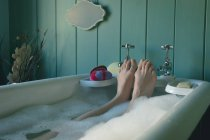 Low section of woman taking bath in bathtub at bathroom — Stock Photo