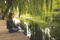 Beautiful woman using mobile phone while sitting near lake side — Stock Photo