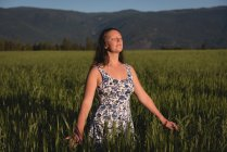 Beautiful woman standing with eyes closed in the field — Stock Photo