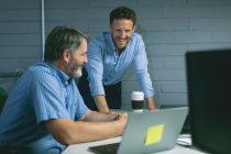 Geschäftskollegen diskutieren über Laptop im Büro — Stockfoto