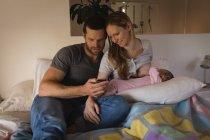 Los padres que usan el teléfono móvil mientras la madre amamanta al bebé en la cama en casa - foto de stock