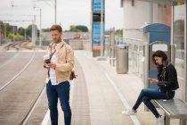Pendolari che utilizzano il telefono cellulare in piattaforma alla stazione ferroviaria — Foto stock