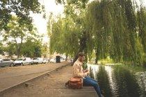 Вид збоку людини, що використовує цифровий планшетний біля озера сторона — стокове фото