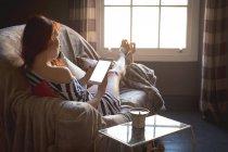Женщина с цифровым планшетом на диване дома — стоковое фото
