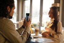 Мужчина фотографирует ее партнера в кафе — стоковое фото