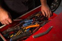 Mecânico masculino remoção ferramentas da gaveta na garagem — Fotografia de Stock