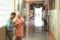 Dirigenti che discute sopra ridurre in pani digitale nel corridoio all'ufficio — Foto stock