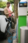 Man using mobile phone while charging electric car at charging station — Stock Photo