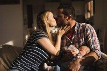 Батьки цілувати один одного, а батько годування дитини на дивані в домашніх умовах — стокове фото