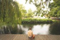Rückansicht eines Mannes, der am Seeufer sitzt — Stockfoto