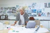 Жіночий виконавчий, дивлячись на креслення на реєстрації в office — стокове фото