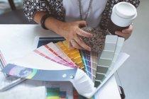 Крупный план женщины-руководителя, проверяющей цветные образцы на чертежном столе в офисе — стоковое фото
