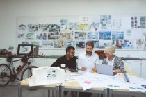 Executives discussing over blueprint at desk in office — Stock Photo