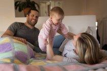 Les parents s'amusent avec bébé sur le lit à la maison — Photo de stock
