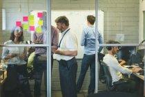 Gens d'affaires discutant sur tablette numérique au bureau — Photo de stock