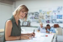 Portrait of female executive working on drafting table in office — Stock Photo