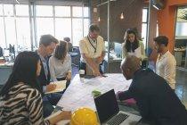 Деловые люди, обсуждая над основой в работе совещания в офисе — стоковое фото