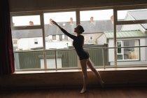 Ballerina pratica la posizione del balletto arabesco in studio di danza — Foto stock