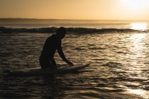 Surfer with surfboard surfing on sea during sunset — Stock Photo