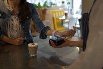 Frau bezahlt mit nfc-Technologie auf Smartwatch im Café — Stockfoto