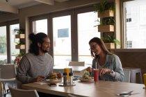 Junges Paar mit Essen im café — Stockfoto