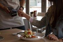 Mujer pagando con tecnología NFC en tarjeta de crédito en cafetería - foto de stock