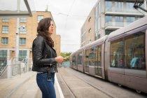 Hermosa mujer con teléfono móvil en la plataforma en la estación - foto de stock