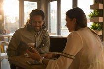 Молода пара обговорення на мобільний телефон у кафе — стокове фото