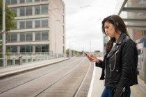 Vista laterale della donna che utilizza il telefono cellulare in piattaforma alla stazione ferroviaria — Foto stock
