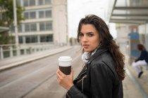 Mulher tomando café na plataforma na estação ferroviária — Fotografia de Stock