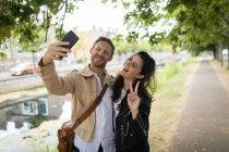 Щаслива пара беручи selfie біля озера сторона — стокове фото