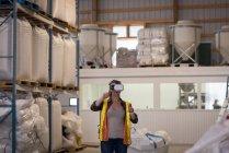 Женщина-работница, использующая гарнитуру виртуальной реальности на складе — стоковое фото