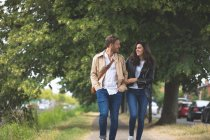 Romantic couple interacting while walking in street — Stock Photo