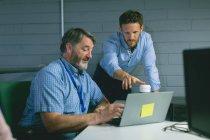 Colegas de negócios discutindo sobre laptop no escritório — Fotografia de Stock