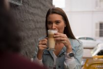 Smiling woman having coffee at outdoor cafe — Stock Photo