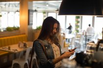 Smiling woman using mobile phone in cafe — Stock Photo