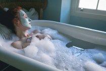 Woman relaxing in bathtub at bathroom — Stock Photo
