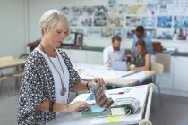 Female executive checking catalog on drafting table in office — Stock Photo