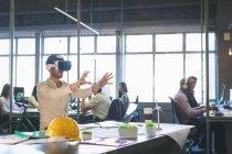 Мужчина, использующий гарнитуру виртуальной реальности в офисе — стоковое фото