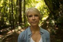 Портрет женщины, стоящей в лесу — стоковое фото