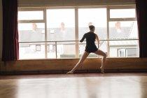 Ballerine s'étirant sur la barre tout en pratiquant la danse de ballet en studio de danse — Photo de stock