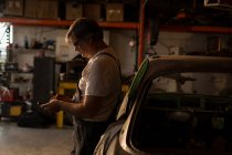 Male mechanic using mobile phone in garage — Stock Photo