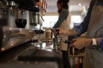 Средняя секция официантки готовит кофе у кофеварки в кафе — стоковое фото
