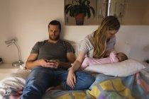 Père utilisant un téléphone portable pendant l'allaitement maternel pour bébé sur le lit à la maison — Photo de stock