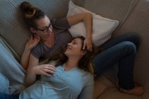 Lesbian couple lying on sofa in living room at home — Stock Photo