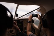 Fotografieren mit dem Handy während des Fluges im Flugzeug-Cockpit Pilot — Stockfoto