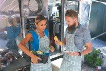 Пара взаємодіють один з одним, поблизу харчової вантажівка — стокове фото