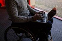Section médiane de l'homme handicapé utilisant un ordinateur portable dans l'atelier — Photo de stock
